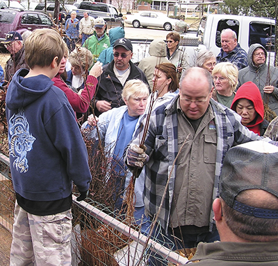 Mike Bailey handing out trees on Arbor Day