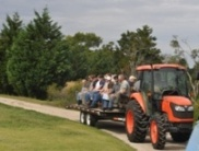 Employees riding on a wagon being pulled by a tractor