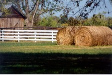 Farm scene with fence and hay bales