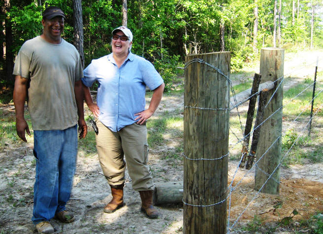 Emanual King and NRCS DC Joyce Nicholas beside fence.