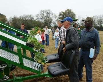 Farmers look at planting equipment.
