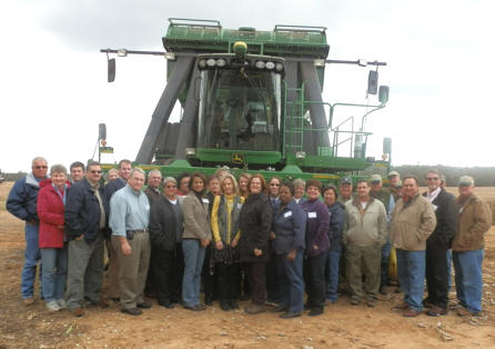 Group photo of tour participants in front of a cotton roll baler.