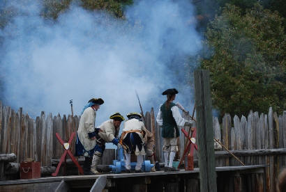 Reenactors fire the fort's cannon.