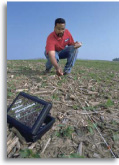 Photo of NRCS employee measuring crop residue in a field.