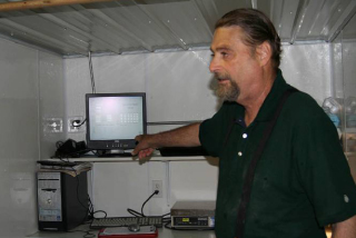 photo of man point at computer while describing egg cleaning process.