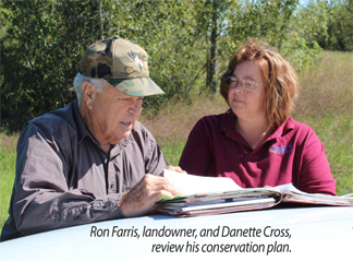 Ron Farris, landowner, and Danette Cross, review his conservation plan.