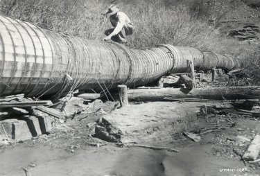 Torrey Irrigation Company owner is shown examining a homemade wooden stave, noting the irregular alignment; weak deteriorated condition and high coefficient of friction