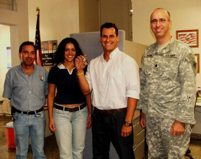 Samuel Rios (second from right) receives Medal of Achievement from U.S. Army Corps Colonel Baker (right).