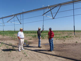Rick Schlegel, NRCS Irrigation Engineer, Tom Moeller, producer, and P.J. Martin, NRCS Student Trainee, discuss pressure regulators on a new LPIC Center Pivot Sprinkler that survived extreme hail damage.