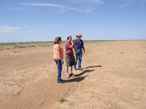 Assistant state climatologist with the Oklahoma Climatological Survey, Gary McManus (center), videos the extreme wind erosion occurring on exposed land. Cimarron County Conservation District employees, Iris Imler, clerk, and Jim Belford, district technician, gave McManus a tour of the devastating area on June 24.