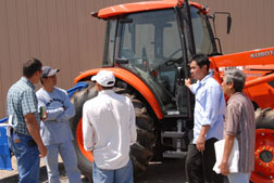 Laotian poultry farmers visit with a Kubota Tractor salesman