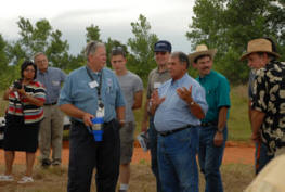 During the tree cutting demonstration at Lake Draper, High Plains RC&D Coordinator Tom Lucas visits with conference participants about the High Plains RC&D cedar removal project on 53 acres near Woodward.