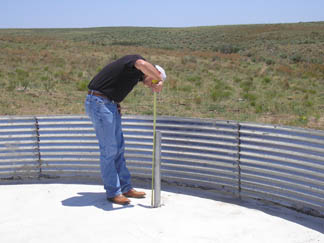 P.J. Martin, Student Trainee, measures overflow on Steel Sidewall Watering Facility to ensure that tank is constructed to specifications and provides adequate storage for watering needs.