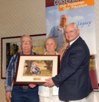 Frank and June Austin receive portrait from State Conservationist Ron Hilliard at OACD meeting.