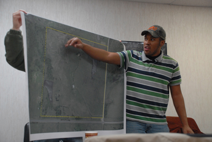 Describing the plan to his classmates, Soil Conservationist Charles Rogers points to the boundary where his team will place extra people to help keep an eye on the fire.