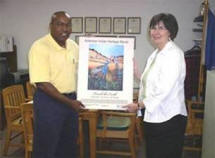 This year�s winning artist Kathy Sturch, Choctaw Nation of Oklahoma, and Arkansas Assistant State Conservationist Anderson Neal, look over the poster one last time before sending it to production.