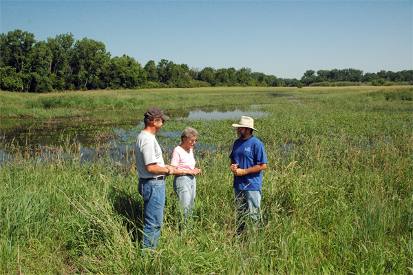 Haeffner (right) talks with Caryl Leopold Smith and son, Nelson, about the 102-acre WRP wetland he helped design.