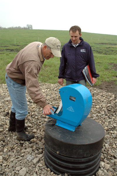 To provide water to cows in three of seven paddocks, Mike Sweeney used a tile line from his pond and an ag waterway to animal powered nose pumps. Sweeney, left, shows NRCS Soil Conservationist Ryan Gerlich how the pumps work. In the other four paddocks, the cows have access to water in Camp Creek at the crossing locations.