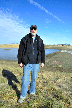 John Aschenbrenner stands in front of his newly created wetland that will help to filter out sediment and farm chemicals before the water outlets to West Lake.