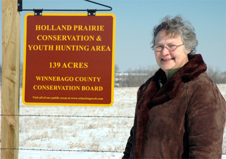 Martha Olson stands in front of a sign that announces the Winnebago County century farm she owns with her sister Diane Rickerl is now northern Iowa�s first �youth hunting� wildlife area. By contract the land is administered by the Winnebago County Conservation Board until 2027 with NRCS holding a permanent Wetlands Reserve Program easement.