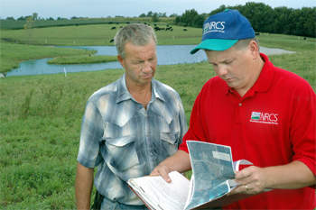 Louisa County Farmer Roger Edwards and NRCS District Conservationist Drew DeLang review Edwards� prescribed grazing conservation plan. Using Environmental Quality Incentives Program cost share, Edwards built fences and a cattle watering system that reduces erosion and makes his grazing land more efficient.