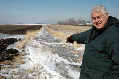 Retired agricultural engineer John Laflen points to his three year old living snow fence.  The plantings of native grasses, trees and shrubs trap blowing and drifting snow on his Winnebago County property to keep the county road to the east from drifting shut and blocking his neighbors until snow plows arrive.  The vegetative barrier was designed by NRCS and enrolled in the continuous CRP living snow fence program.