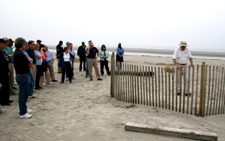 SC Earth Team Volunteer Bill Wilkes demonstrates how to install sand fencing to protect dunes.