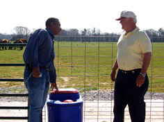 NRCS Soil Technician John Bennett, (left), discusses the use of heavy use area water troughs with William Amerson.