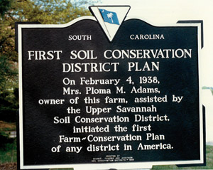Picture of a sign showing the first Farm-Conservation Plan of any district in America at the farm of Mrs. Ploma A. Adams, in Oconee County, SC in 1938.