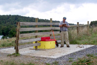 After: Mike Phillips measures pipeline and one of the installed watering troughs.