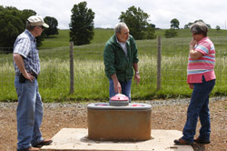 Yancey, Nelson, and Ann Evans inspect a new watering trough.
