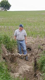 Photo of NRCS Conservationist standing in a ditch.