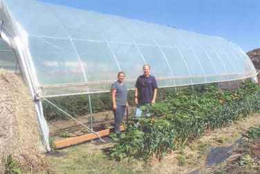 Maria Stewart and Steve Wingerson with a seasonal high tunnel