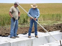Mike Clover (right) is demonstrating how to use a survey rod to a volunteer.