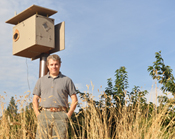 Mike Omeg standing next to an owl box on his property.