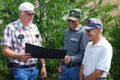 NRCS District Conservationist David Chain (left) with landowners Ron Hjort and Mike Horton.