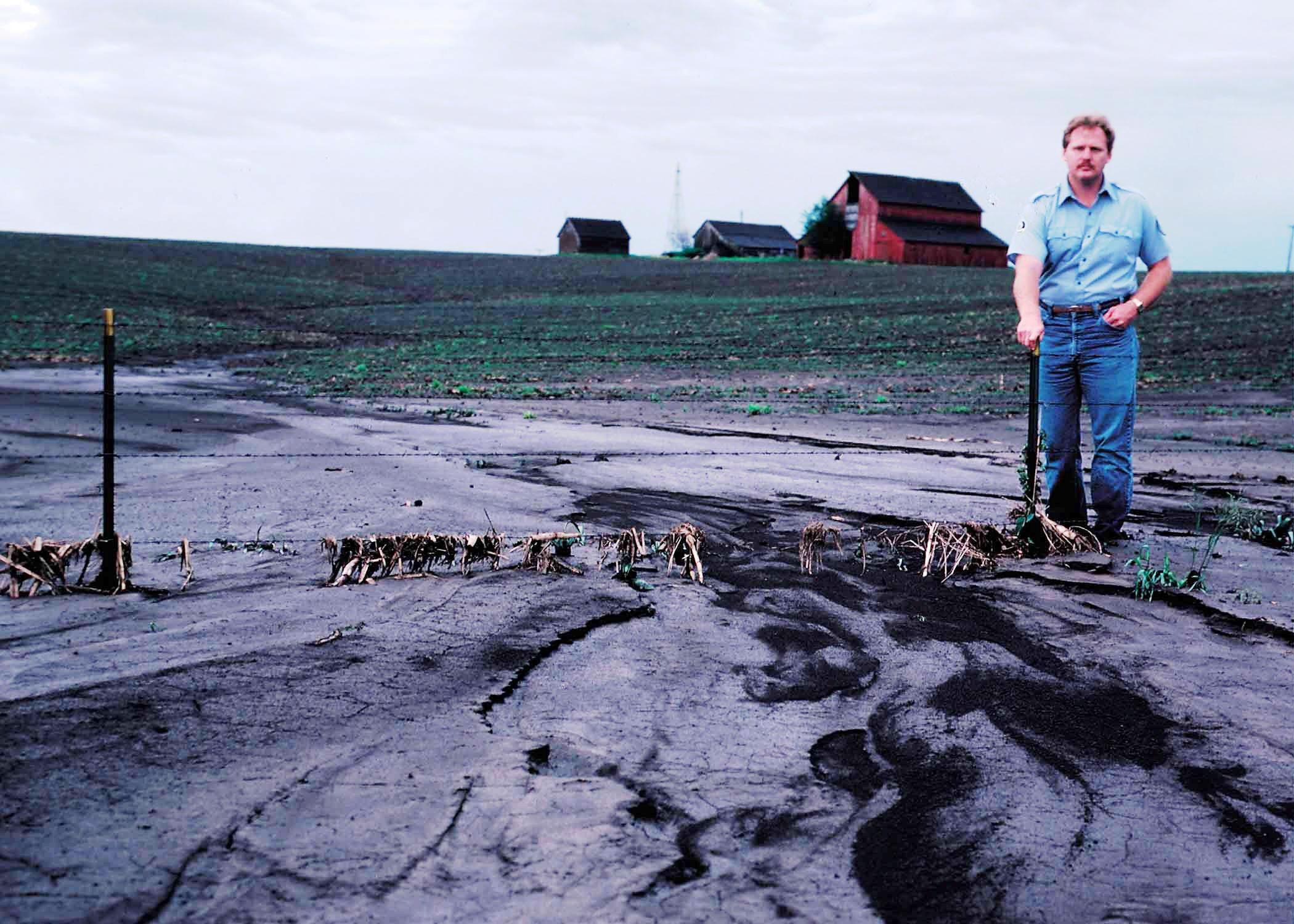 Man standing near sediment coming from severely eroded crop field.
