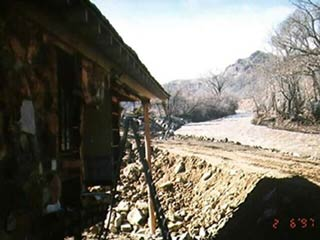 Photo of constricted river channel and damaged house