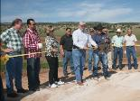 Dennis Alexander, New Mexico conservationist, front left, and Alex Gonzales, front right, chair of the Lava Soil and Water Conservation District, demonstrate their ribbon-cutting skills at the Prop Canyon dam's Aug. 27 ceremony. Looking on are state, county and city officials plus area residents. Cibola Beacon image.