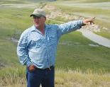 Clay �una�McAlpine points to the original water flow, through coulees located on land he farms, with the new piped water flow behind him. Photo by Hayli Thompson.