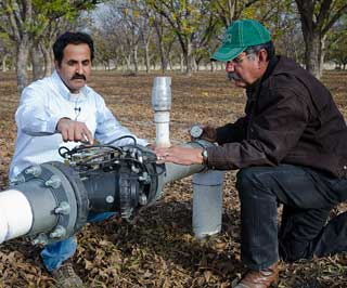 Arrowhead Farms owner Mr. Akram Mohammad (left) talks with Natural Resources and Conservation Service (NRCS) District Conservationist J.M. Villarreal (right) about the pressure control valves used at the pecan orchards at Arrowhead Farms.