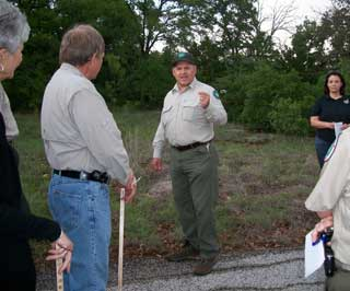 With a group of visitors at the Pasture Walk held at Lake Mineral Wells State Park and Trailway, David Owens, Texas Parks and Wildlife Department, discusses plant identification characteristics and points out important plants to the group.