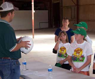 Overton shows children the proper safety helmet, goggles, clothing and footwear to be used when operating an ATV.