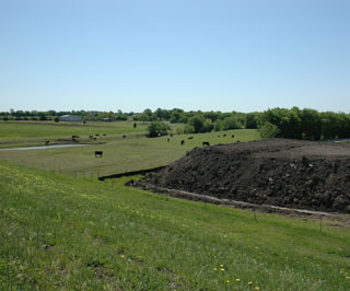 This photograph shows the landscape surrounding the back slope of Pilot Grove dam No. 28 with the impact basin in the background and removed top soil in the mixing area.