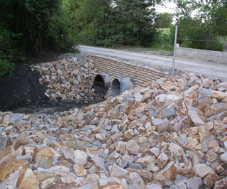 A completed sand cement bag riprap wall with rock riprap chutes.