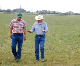 Urban sprawl has encroached on the ranch�s borders where he farms his rice, raises his cattle and works to be a steward of the land leaving it better off than he found it. Trey Bethke (left) a NRCS district conservationist visits with Dollins as they assess a fallow rice field now being used for grazing cattle.