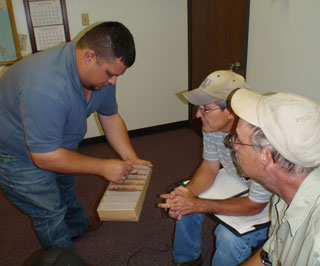 Roel Guerra Jr., Soil Survey 133B Soil Survey Party Leader, and Louisiana Soil Scientists Marc Bordelon, and Joel Bolin examining a sample in a soil correlation box. (left to right) Roel Guerra Jr., Marc Bordelon, Joel Bolin.