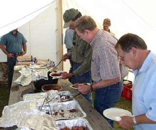 Association members going through the meal line for brisket, sausage, German potato salad, red beans, and bread pudding.