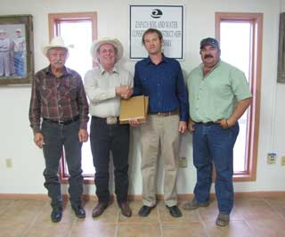 Jose O. Dodier, chairman of the Zapata County SWCD, is presented the Zapata County soil survey manuscript from Clark Harshbarger. (Pictured from left to right) Horacio Gonzalez, Jose O. Dodier, Jr., Clark Harshbarger, and Fernando Munoz, Jr.