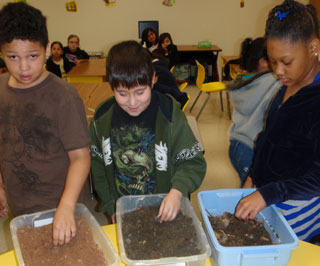 Fourth graders getting their hands dirty during the hands-on demonstration--texturing sand, silt, and clay soils as well as the high organic matter (humus) soils.